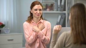 Offerta femminile sorda abbracciare amico, conversazione nel linguaggio dei segni, dialogo video d archivio