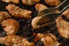 Offerte cotte del pollo su una griglia del carbone di legna immagine stock
