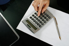 Office. Typing numbers for income tax return with pen and calculator stock photo