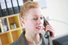 Office. Image taken of a receptionist with a phone calling a company Royalty Free Stock Images