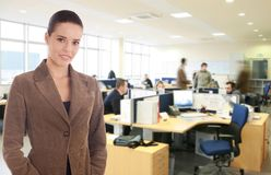 At the office. Young businesswoman standing at the busy office Royalty Free Stock Images