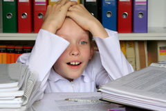 In the office. Young girl having too much work Royalty Free Stock Image