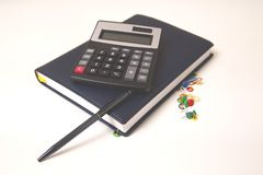 Office accessories with calculator and notepad on desk stock image