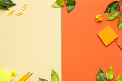 Office Accessories with Leaves on Yellow and Orange Background Royalty Free Stock Photo