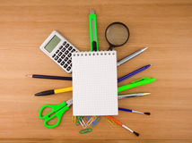 Office accessories under checked notebook on wood royalty free stock image