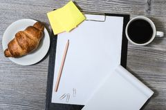 Office accessorise on wooden gray table: clipboard, cup of coffe. E, fresh croissant Stock Images