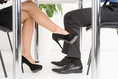 The Office Affair. Woman's foot looking for man's foot under a business table stock photography
