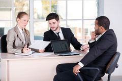 Office affairs. Three successful business people sitting in the Royalty Free Stock Image