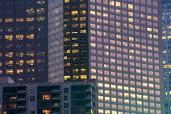 Office and Apartment Buildings at Night. Adjoining office buildings show all kinds of work going on even after dark. An apartment building is in the foreground stock photos