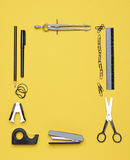 Office Back to School Supplies. Office and back to school supplies on a yellow background. Looking down on the all black and chrome tools from an overhead angle royalty free stock photography