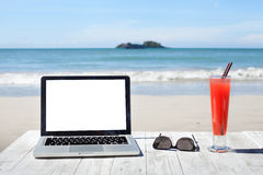 Office on the beach, laptop. With empty screen, sunglasses and tropical cocktail Royalty Free Stock Photo