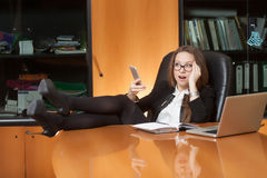 Office beautiful lady making selfie. Office lady making selfie on the black leather chair with foot on the table Stock Photos