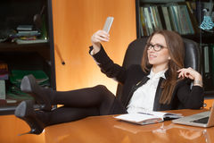 Office beautiful lady making selfie. Office lady making selfie on the black leather chair with foot on the table Royalty Free Stock Photo