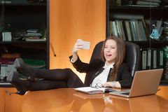 Office beautiful lady making selfie. Office lady making selfie on the black leather chair with foot on the table Stock Photo