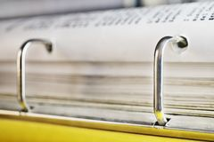 Office binder. Open yellow binder close up , stack of white papers and bright metal rings , in the background black text out of focus royalty free stock photos