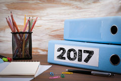 2017 Office Binder on Wooden Desk. On the table colored pencils, pen, notebook paper.  Stock Photos