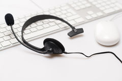 Office black headphones on white keyboard Royalty Free Stock Photos