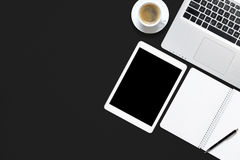 Office black work desk table with laptop, tablet, cup of coffee and blank note book. royalty free stock images