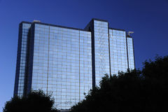 Office block. An office block rises above trees silhouetted in the foreground Stock Image