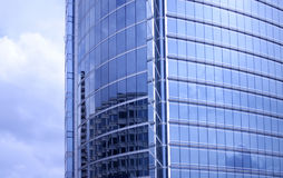 Office building. Blue office building with reflection of clouds and other building Royalty Free Stock Photos