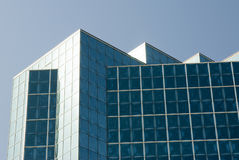 Office Building. Detail of the architecture of a modern office building with reflective glass exterior windows. Clear blue sky Royalty Free Stock Photography