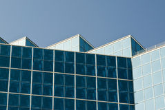 Office Building. Detail of the architecture of a modern office building with reflective glass exterior windows. Clear blue sky Royalty Free Stock Images