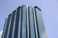 Office Building. Angled shot of an office building with shiny blue glass facade on a sunny day Stock Image
