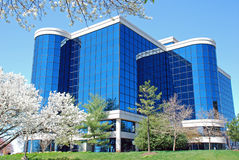 Office building 21. Striking office building with a facade of blue reflective glass and white trim  Surrounded by flowering trees and landscaping Stock Photo
