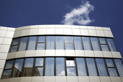 Office building. And a small cloud on a blue sky Stock Images