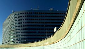 Office building. Nice looking office building with a rough curvy wall in front Royalty Free Stock Photography