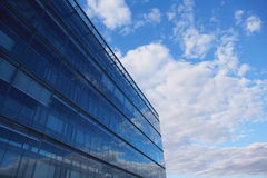 Office Building. Sky and glass wall of an office building, reflections of clouds Stock Image