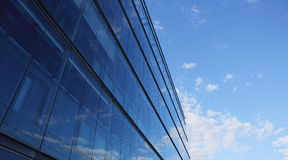 Office Building. Glass wall of an office building, reflections of clouds Royalty Free Stock Photos
