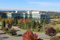 Office Building with Autumn Foliage. Exterior of a modern office building at Bellevue, Washington with trees turning colors in Autumn on a sunny day and downtown royalty free stock image