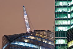 Office building and crane. Offices skyscraper with illuminated crane on background stock images