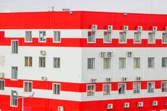 Office building distribution center. With a variety of windows and air conditioners. sandwich panels painted in red and white royalty free stock images