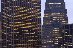 Office Building at Dusk. The lights come on in two modern skyscrapers as dusk settles over the city royalty free stock photos
