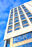 Office building on a background of blue sky. Office building elongated with large glass windows on a background of blue sky Royalty Free Stock Photos