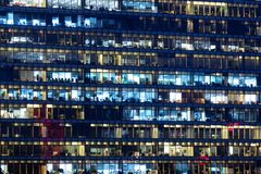 Office building exterior in the late evening with interior lights. Business people working in the evening. Illuminated office. Building royalty free stock photography
