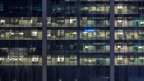 Office building exterior during late evening with interior lights on and people working inside night timelapse