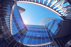 Office building from low angle. Blue sky and flare reflections. Royalty Free Stock Image