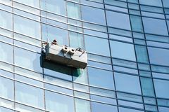 Office building maintenance, facade cleaning. Office building maintenance, glass facade cleaning with cradle royalty free stock photography