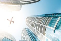Office building / modern skyscraper buildings, sky and airplane Stock Photo