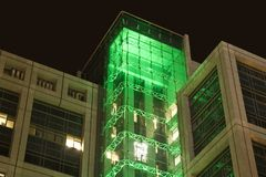 Office building at night with green lights. Office buildings at night with glass facade illuminated with green light and trans[arent elevator Stock Image