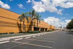Office building with parking spaces. Side of office building with parking spaces and palm trees Stock Images