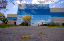 Office Building with Reflection. An office building in the fall, sky reflected in the wall panels. Negative space of sidewalk with leaves in the foreground royalty free stock photo