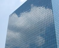 Office Building Reflection. Cumulus clouds are reflected perfectly in the rectangular windows of a modern office building Stock Image