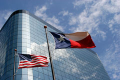 Office building in Texas. American and Texas flags in front of a skyscraper Stock Photo