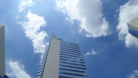 Office building under White clouds and blue sky on the warmest noon in Thailand. White clouds in warmest day in Bangkok Stock Photos