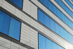 Office building wall. Modern office building wall with blue glass windows royalty free stock photo