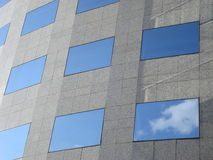 Office building wall with rectangular windows reflecting the sky Royalty Free Stock Image